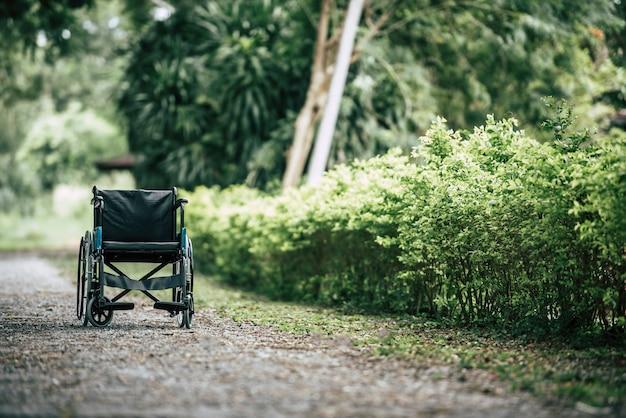 Cadeira de rodas vazia estacionada no parque, conceito dos cuidados médicos.