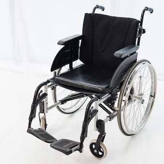 Cadeira de rodas vazia estacionada no quarto