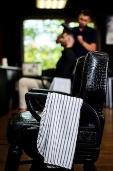Cadeira de salão de cabeleireiro com toalha na poltrona