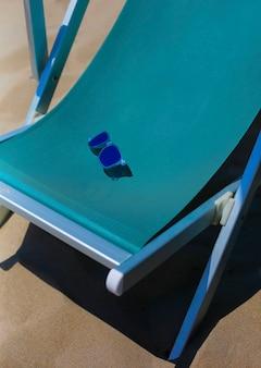 Cadeira de têxteis chaise longue close-up com óculos de sol, férias na praia