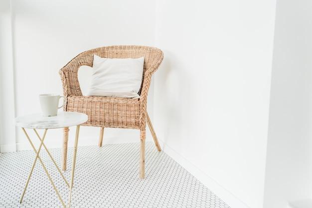Cadeira de vime com travesseiro e mesa de centro de mármore em loggia com piso de mosaico
