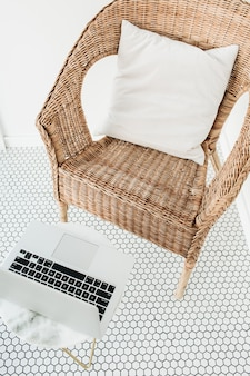 Cadeira de vime com travesseiro e mesa de centro de mármore na varanda com piso de mosaico