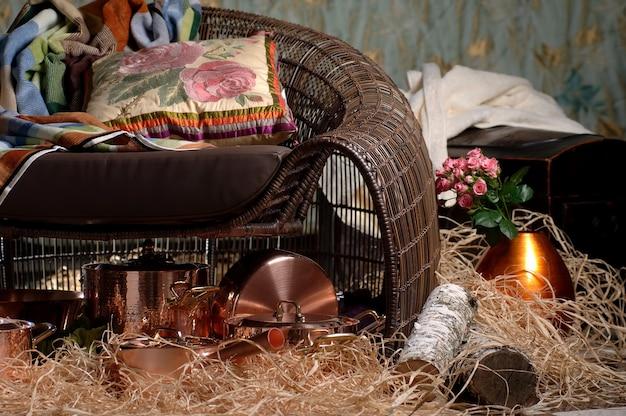 Cadeira de vime com um travesseiro e pratos de metal de bronze