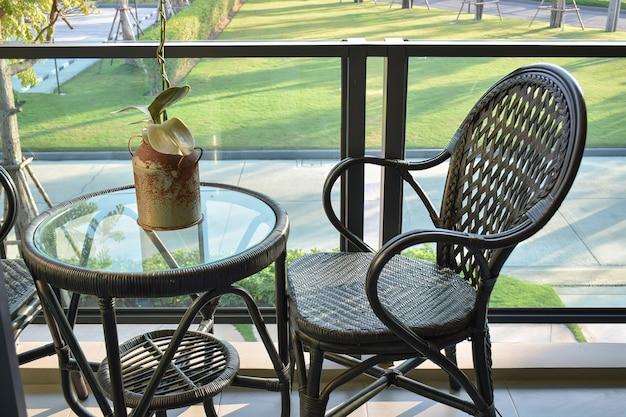 Cadeira de vime marrom na varanda moderna com vista para um jardim