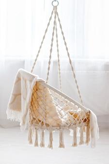Cadeira de vime pendurada com manta bege em casa