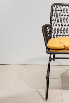 Cadeira de vime preta com detalhes de travesseiros amarelos