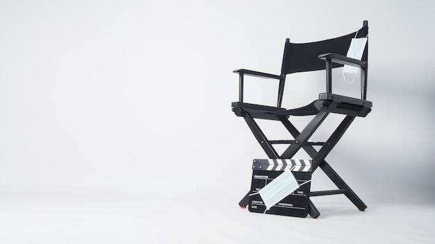 Cadeira do diretor com uma máscara facial suspensa e capa de claquete preta na máscara facial. é usado na produção de vídeo e na indústria do cinema em fundo branco.