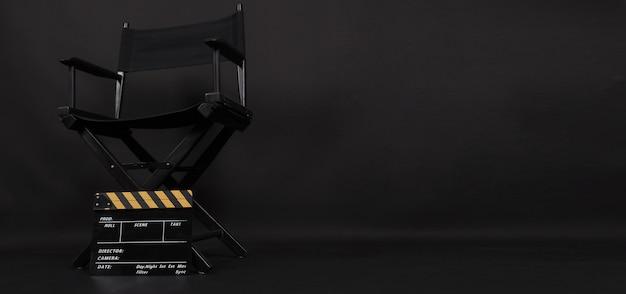 Cadeira do diretor e claquete ou tela de cinema para uso na produção de vídeo ou na indústria cinematográfica. é colocado em um fundo preto.