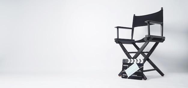 Cadeira do diretor e claquete ou tela de cinema preta com máscara facial. é usado na produção de vídeo e na indústria do cinema em fundo branco.