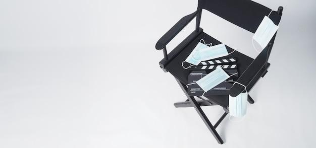 Cadeira do diretor, máscara facial e claquete ou tela de cinema preta. é usado na produção de vídeo e na indústria do cinema em fundo branco.