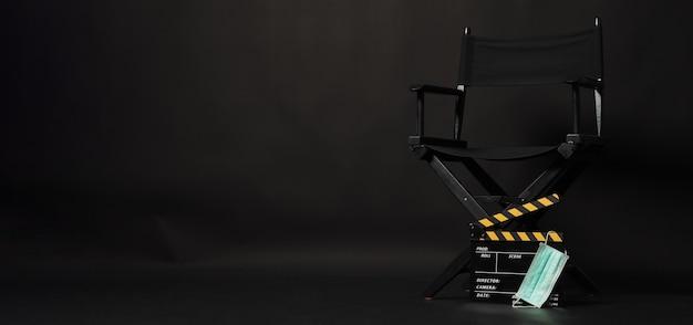 Cadeira do diretor preta e claquete ou ardósia amarela com máscara facial e megafone em fundo preto.