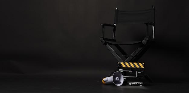Cadeira do diretor preta e claquete ou claquete de cinema com megafone amarelo sobre fundo preto. use na produção de vídeo ou na indústria do cinema cinematográfico