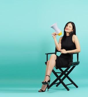 Cadeira do diretor preto e mulher asiática é segurar o megafone e sentado nele. coloque a cor verde hortelã ou fundo azul tiffany.