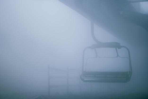 Cadeira do teleférico e nevoeiro.