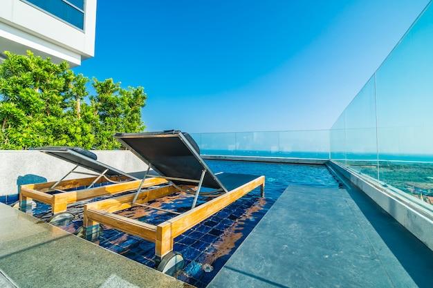 Cadeira e cama ao redor da piscina no hotel
