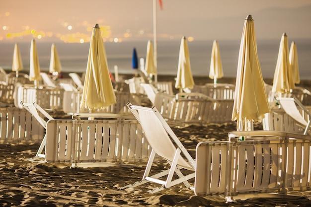 Cadeira e guarda-chuva na costa. foto da noite no mar. viajando na europa. céu de verão na itália. guarda-chuva na costa do mar. lugar para relaxar na praia. paisagem linda noite. noite quente de verão.