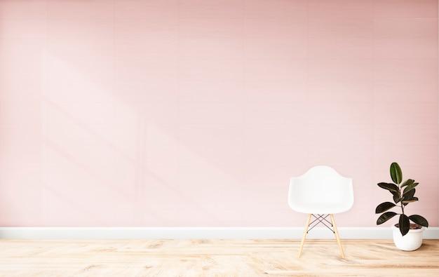 Cadeira e uma planta contra uma parede rosa