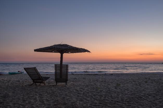Cadeira, guarda-chuva, pôr do sol de noite de praia à beira-mar.