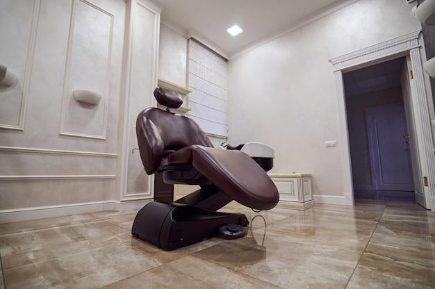 Cadeira marrom vazia na barbearia ou salão de beleza. design de interiores luxuoso