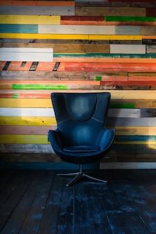 Cadeira moderna de ovo em uma parede de madeira colorida