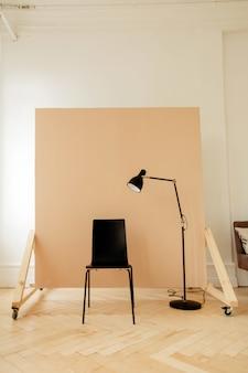 Cadeira preta com lâmpada no quarto para sessão de fotos