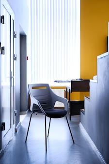 Cadeira preta no corredor do apartamento, foto real com espaço de cópia na parede branca