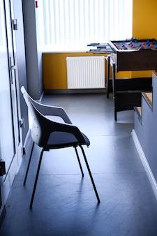 Cadeira preta no corredor do apartamento