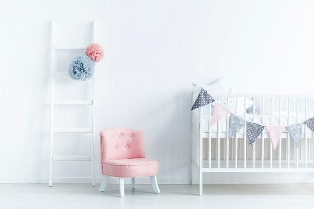 Cadeira rosa ao lado do berço branco no interior do quarto do bebê em tons pastéis com escada. foto real