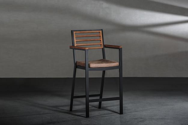 Cadeira simples com pernas altas metálicas em uma sala com paredes cinza