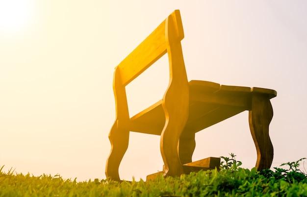 Cadeira velha de cadeiras longas na grama verde com luz solar