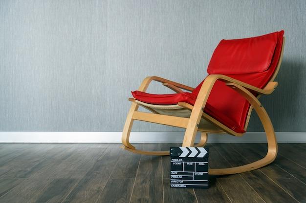 Cadeira vermelha e claquete com espaço para texto