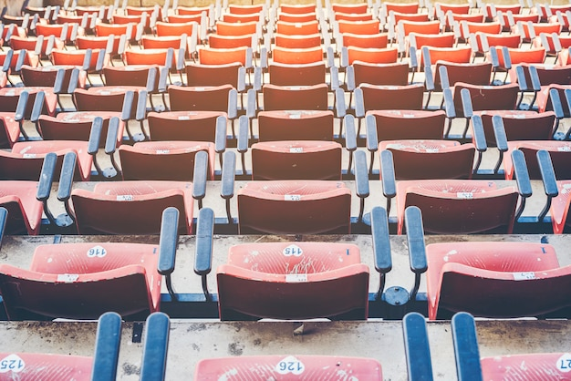 Cadeira vermelha vazia velha do estádio no estádio.