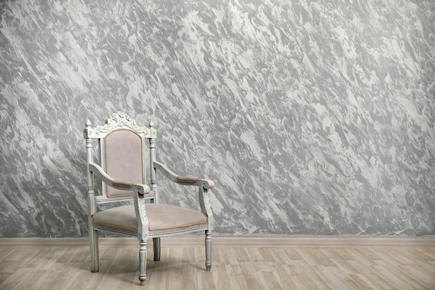 Cadeira vintage contra uma parede cinza texturizada.