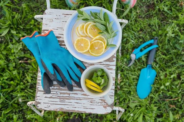 Cadeira vintage, tesouras de podar, ferramentas, luvas, xícara de chá de ervas frescas com hortelã e limão