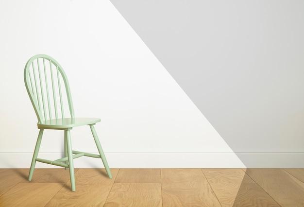 Cadeira vintage verde em uma sala vazia com piso de madeira e parede branca