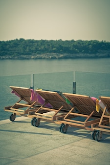 Cadeiras à beira da piscina do hotel com vista para o mar. foto vertical estilo vintage