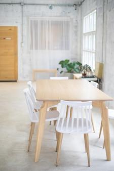 Cadeiras brancas e mesa de madeira na sala