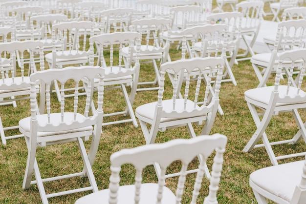 Cadeiras brancas elegantes em um gramado criado para cerimônia de casamento
