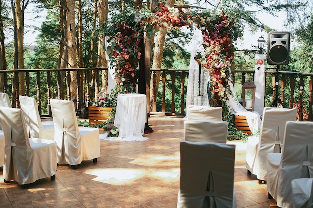 Cadeiras brancas estão diante do altar do casamento na varanda