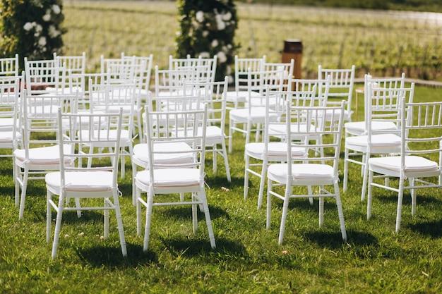 Cadeiras brancas na grama na frente do arco de cerimônia de casamento