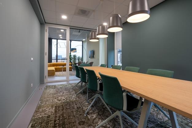 Cadeiras colocadas ao lado de uma mesa em uma sala com um tapete estampado