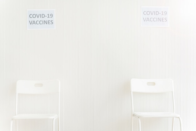 Cadeiras colocadas na estação de espera para receber a vacina covid na clínica ou hospital com parede branca