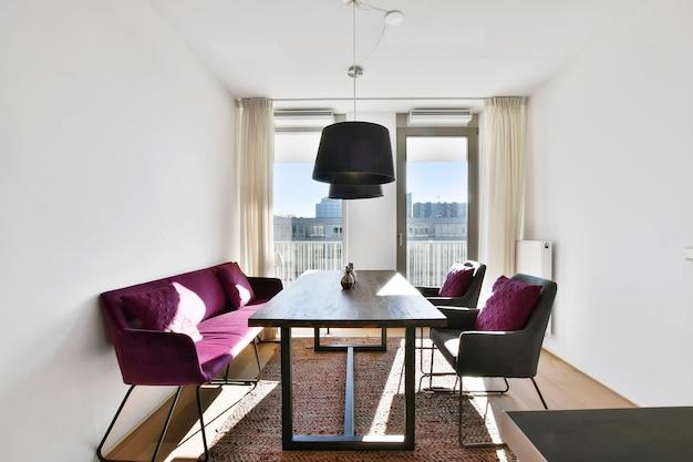 Cadeiras confortáveis com almofadas e sofá localizados perto da mesa sob lâmpadas na elegante sala de jantar em apartamento contemporâneo