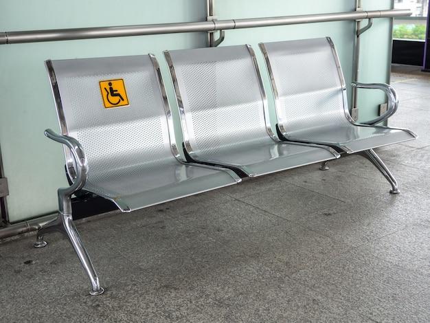 Cadeiras de aço inoxidável na estação de trem com sinalização desativada para facilitar o uso