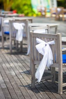 Cadeiras de casamento decoradas com laços brancos no café ao ar livre
