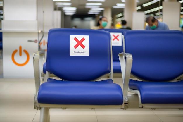 Cadeiras de distanciamento social no aeroporto internacional, conceito de prevenção do coronavirus.