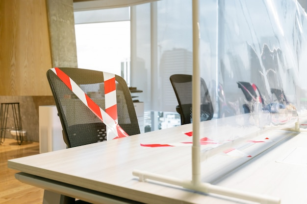 Cadeiras de escritório marcadas com fita branca e vermelha e bloqueadas com a parede física de plástico.
