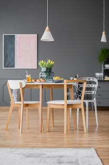 Cadeiras de jantar modernas de design criativo em torno de uma mesa de cozinha simples com uma toalha de mesa cinza