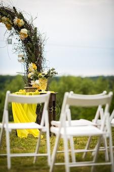Cadeiras de jardim brancas estão diante do altar do casamento feito de osier
