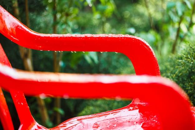 Cadeiras de jardim de plástico vermelho no terraço ao ar livre no jardim da casa após a chuva.